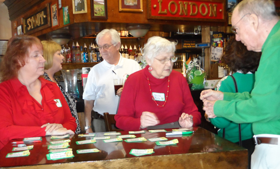 Treasurer Evelyn Frazier, Membership Director Patti Winston and President RIchard Welch watch while Shirley Kelly sells John O'Neill a raffle ticket.
